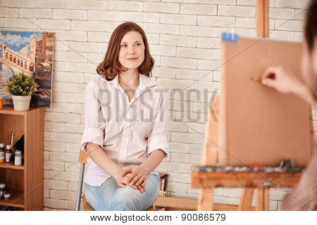 Young woman posing for artist in studio