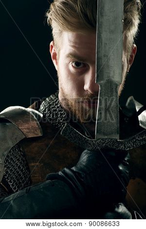 Ancient knight in metal armor with sword on gray background