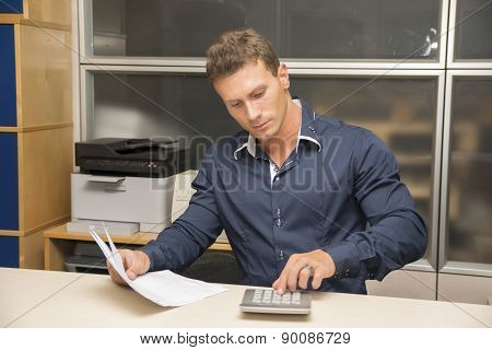 Handsome male office worker using calculator
