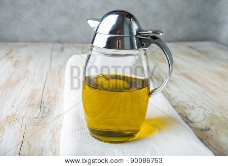 Olive Oil In A Jug On A White Wood