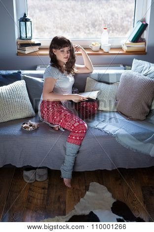 Young beautiful woman sitting home on the couch wearing christmas print pajamas reading book