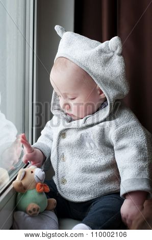 Cute Happy Baby Boy  Sitting Near The Window