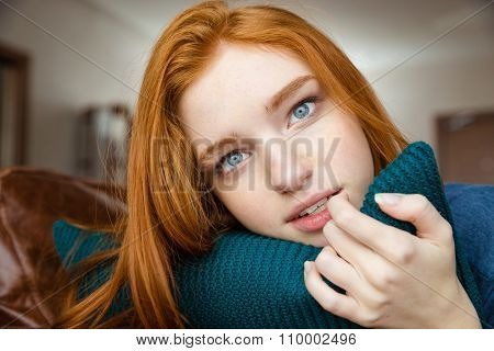 Thoughtful attractive redhead young lady hugging knitted pillow