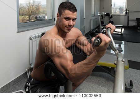 Man In The Gym Exercising Biceps On Machine