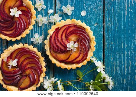 Tarts With Plum On Blue Wooden Background