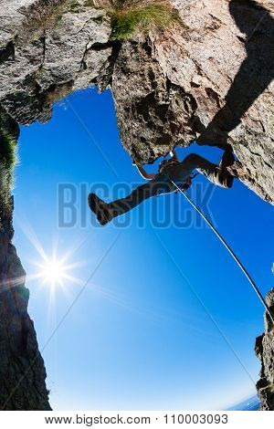 Rock climbing. Male climber on a steep rocky cliff. Sunny day, summer season.