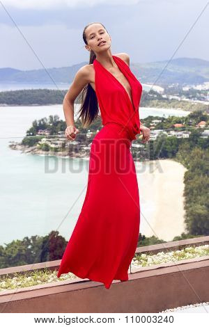 Fashion woman in red dress posing on tropical sea view. New year ball. Phuket island, Thailand