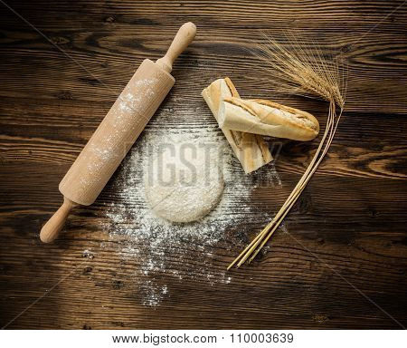 Yeast dough on table with rolling pin and baguette, shot from above