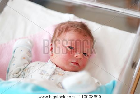 One day old newborn baby in bed