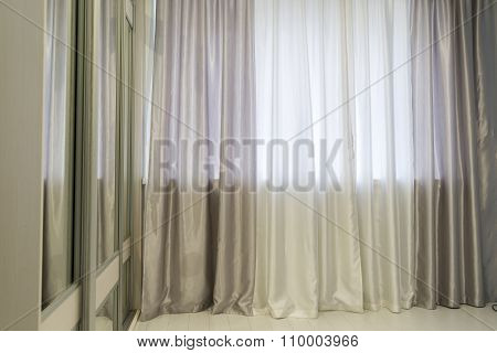 Fragments of silk curtains on  window