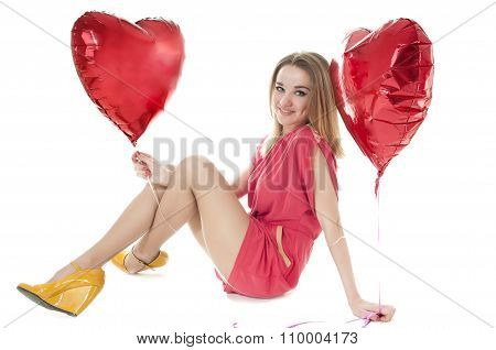 Young Woman With A Heart-shaped Balloons Sitting On A White Background