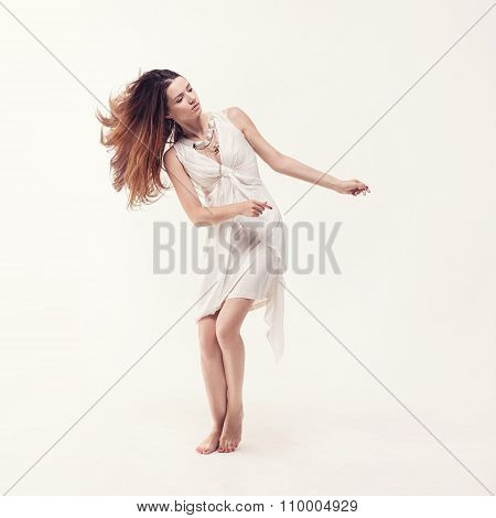 young beautiful dancer in white dress posing