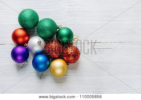 Colored Christmas Decorations On A White Wooden Table.
