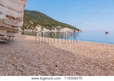 Sandy beach with blue sea and mountains