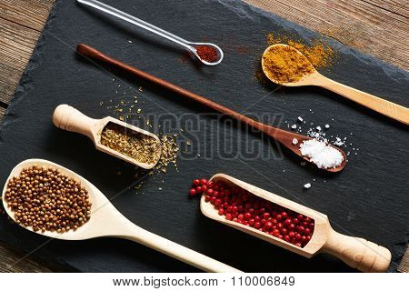 Spices in wooden utensils over slate