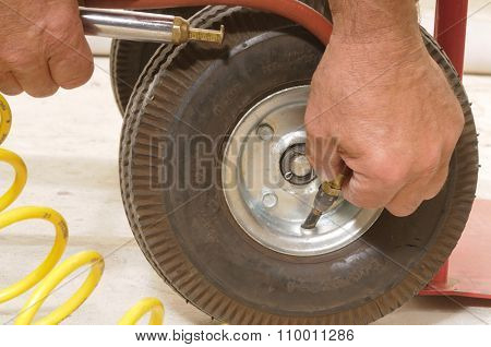 Mechanic putting air in the small tire of a hand cart