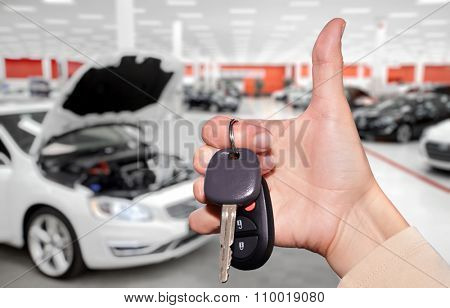 Driver hand with a car key over new vehicle background.