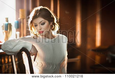 Young sensual woman sitting with window in background. Beautiful girl with white comfortable blouse