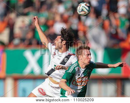 VIENNA, AUSTRIA - SEPTEMBER 20, 2014: Nemanja Rnic (#15 Wolfsberg) and Robert Beric (#9 Rapid) fight for the ball in an Austrian soccer league game.