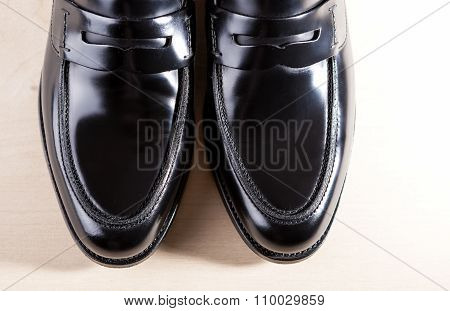 Footwear Concepts. Pair Of Stylish Fashionable Real Leather Black Penny Loafers. Placed On Wooden Su