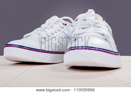 Pair Of White Fashionable Leather Trainers On Wooden Surface Against Gray Background