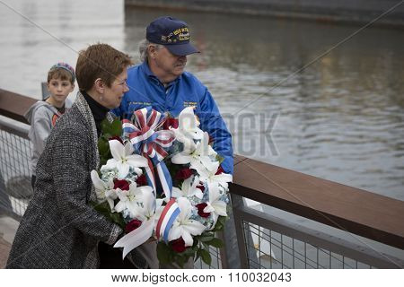 NEW YORK - NOV 25 2015: Army vet Loree Sutton, Commissioner of NYC Mayors Office of Veterans Affairs and former USS Intrepid crew member Tom Wargo toss a wreath into the Hudson River on Veterans Day.
