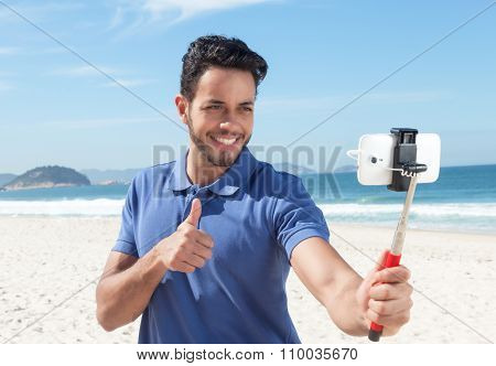 Guy With Blue Shirt And Beard At Beach Taking Selfie With Stick