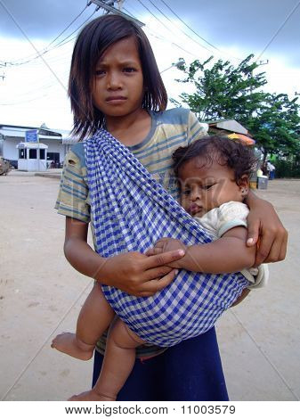 Young Cambodian girl carries her sister and begs for money, Cambodia