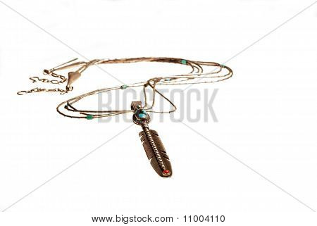 Closeup of silver turquoise and coral pendant in form of feather handcrafted by Native American silversmith and isolated on white background. poster