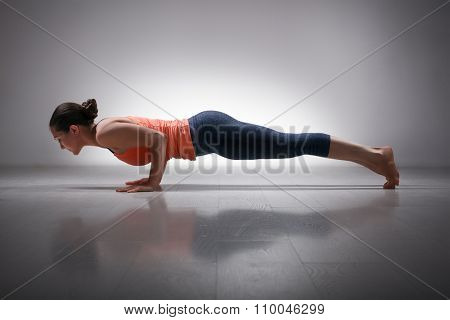 Beautiful sporty fit woman practices Ashtanga Vinyasa yoga Surya Namaskar Sun Salutation asana Chaturanga Dandasana - four-limbed staff pose