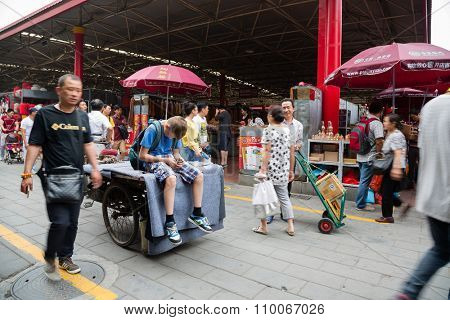 BEIJING - CIRCA JUNE, 2015: European boy sitting on a trishaw and uses smartphone being on the Panjiayuan Antique Market - one of best antiques market in China. Area shopping area of square meters