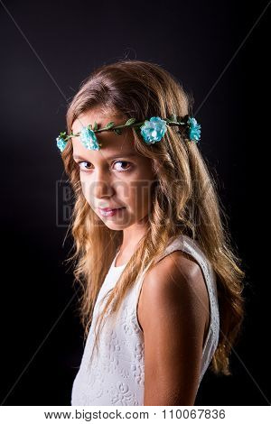 Young Girl With Flower Tiara And Sober Look On Black Background
