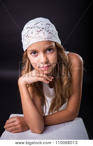 Young Girl With White Cap On Black Background