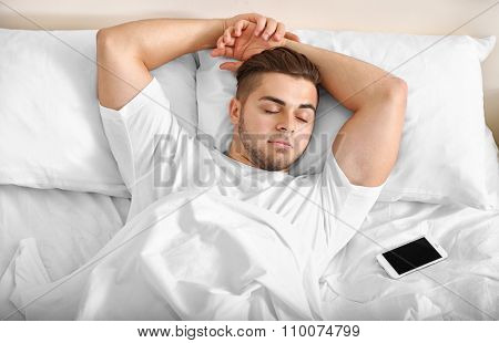 Beautiful young man snoozing on bed