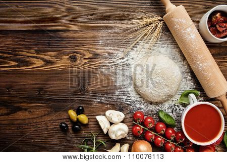 Pizza dough with ingredients on wood, shot from above