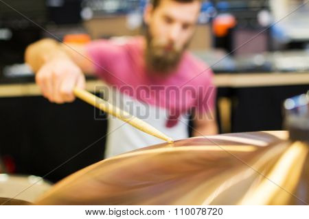 music, sale, people, musical instruments and entertainment concept - close up of male musician playing cymbals at music store