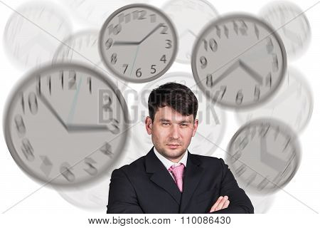 Businesswoman stands among clocks.
