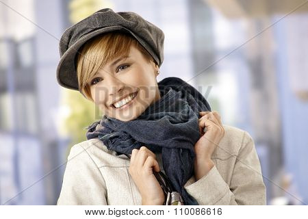 Outdoor portrait of attractive young woman in winter clothes, smiling.