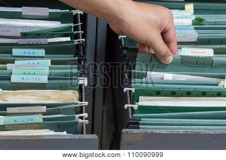 Hand holding top secret file in filing cabinet poster