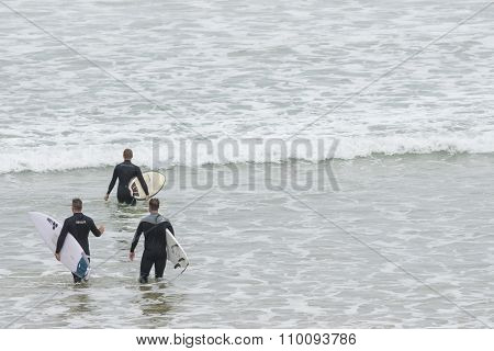 Three surfers walking into the water on a beach
