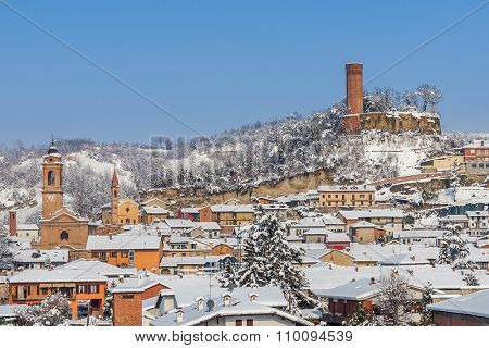 Small town covered with snow on sunny winter day in Piedmont, Northern Italy.