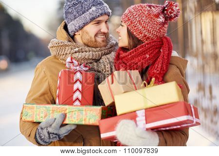 Amorous couple with gift-boxes looking at one another outdoors