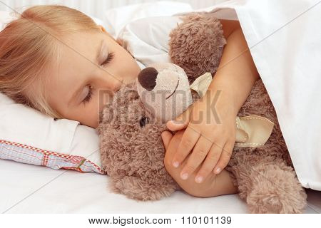 Little girl sleeping in bed with her teddy bear