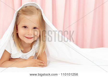 Little girl under the blanket
