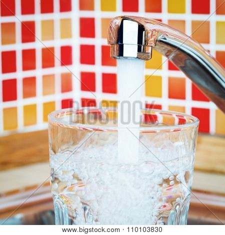 Filling up a glass of fresh water from a kitchen faucet