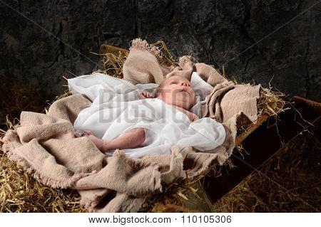 Jesus resting on manger in old barn