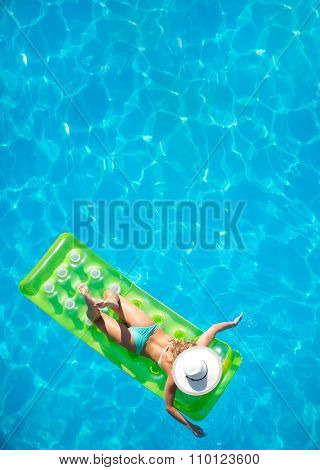 Top view of a  girl in the swimming pool on a lilo air matress