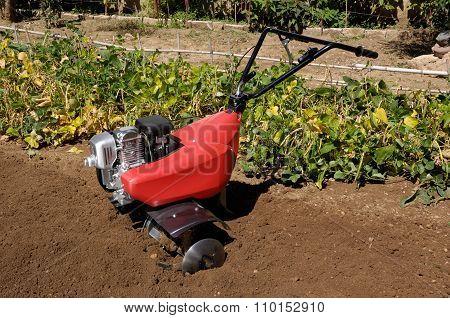A farm power tiller in a garden
