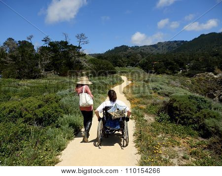 Two Young Women, One Standing And One In Wheelchair, On Dirt Path In Nature Area