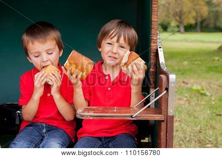 Two Kids, Sitting In A Sheltered Bench, Eating Sandwiches